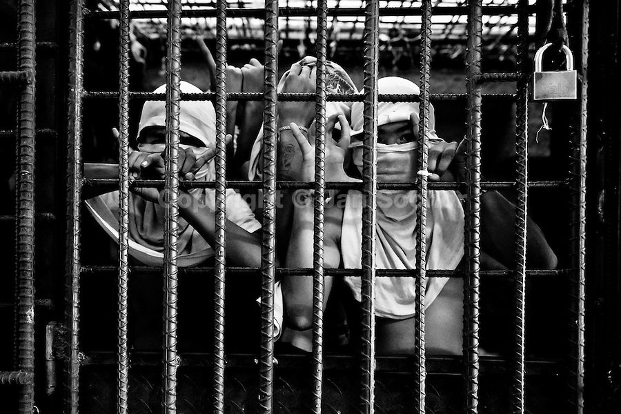 The Mara Salvatrucha gang members show finger signs representing their gang while being detained in the cell of a detention center in San Salvador, El Salvador, 20 February 2014. During the last two decades, Central America has become the deadliest region in the world that is not at war. According to the UN statistics, more people per capita were killed in El Salvador than in Iraq, in recent years. Due to the criminal activities of Mara Salvatrucha (MS-13) and 18th Street Gang (M-18), the two major street gangs in El Salvador, the country has fallen into the spiral of fear, violence and death. Thousands of Mara gang members, both on the streets or in the overcrowded prisons, organize and run extortions, distribution of drugs and kidnappings. Tattooed armed young men, mainly from the poorest neighborhoods, fight unmerciful turf battles with their coevals from the rival gang, balancing between life and death every day. Twenty years after the devastating civil war, a social war has paralyzed the nation of El Salvador.