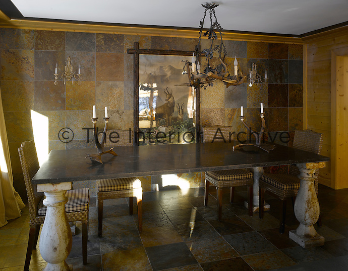 The dining room features a chandelier and a pair of candelabra fashioned out of antlers with walls and floor covered in matching tiles