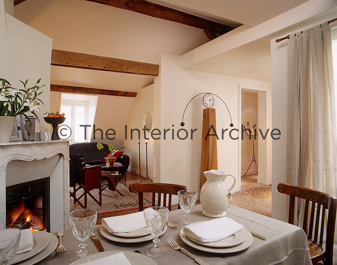 In this open-plan living space a dining table situated adjacent to the fire is laid for dinner on an elegant grey linen cloth
