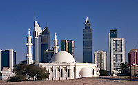 Dubai, United Arab Emirates. Modern buildings on Sheikh Zayed Road, the Abu Dhabi Road, with mosque in foreground..