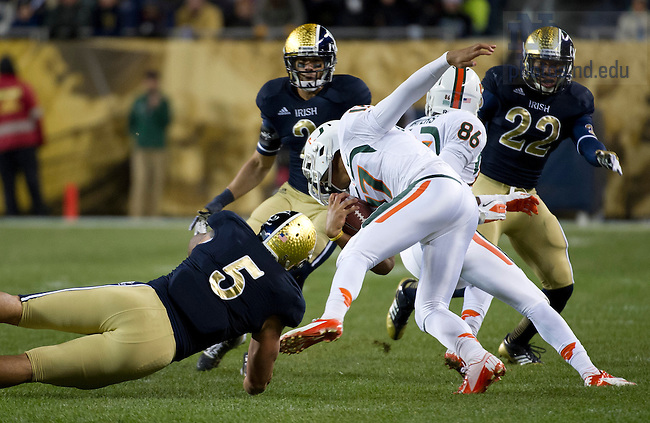 Oct. 6, 2012; Linebacker Manti Te'o trips up Miami quarterback Stephen Morris during the third quarter of the Shamrock Series at Soldier Field in Chicago. Photo by Barbara Johnston/University of Notre Dame..