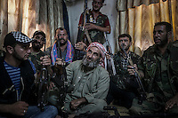 "SHEIK SALAM, leader of a rebel faction of the FSA in Ibeen town, takes a rest with a unit of his men inside a security house, after patroling the city which belongs to the so called ""liberated territory"" under control of the rebels."