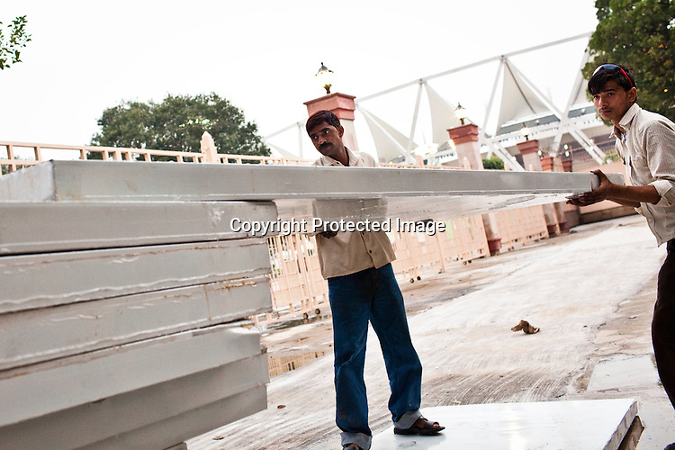 Indian labourers are seen placing the temporary shed floors outside the main stadium for the approaching 19th Commonwealth Games 2010 in New Delhi, India.
