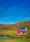 Rural farm scene in West Virginia mountains with fall foliage in the background and a red barn and pond in the foreground.  Image is vertical