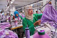 Selem, Garment Factory, Gafsa, Tunisia 2017<br /> Selem sews in a garment factory in the economically challenged town of Gafsa. Of the six countries involved with the Arab Spring protests of the early 2010's, only Tunisia has embraced democracy. Recent acts of terrorism in this country have halted its thriving tourism industry, creating a drastic downturn in the economy. Jobs have become scarce, especially for young girls in already low-income areas, which has created a large gateway for ISIS and terrorism recruitment. The situation has become so dire that the government has enforced a ban on women under the age flying alone. Marn-Tex, the factory shown here, is a supplier to Benetton and was started by a Hedia, a local woman determined to eradicate this recruitment crisis. There are about 120 workers here and about 100 of whom are women. Most of the workers make about $400 dinar ($160) a month.