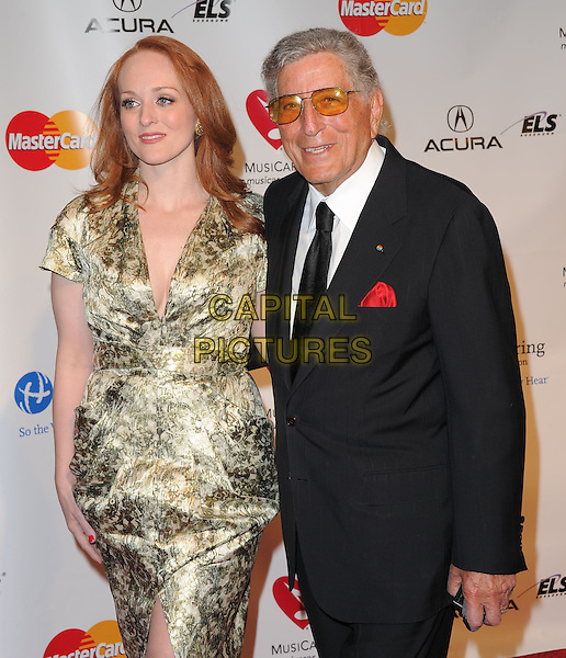 GUEST & TONY BENNETT .at The 2011  MusiCares Person of the Year Dinner at the Los Angeles Convention Center, West Hall in Los Angeles, California, USA, .February 11th 2011..half length dress gold print  glasses black tie white shirt suit .CAP/RKE/DVS.©DVS/RockinExposures/Capital Pictures.