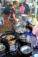 """Two wood-burning stoves set up in an open-air restaurant, to make the ever-popular """"banh khot"""" (a small Vietnamese pancake), specialty of the southern coastal province of Ba Ria-Vung Tau, and especially of Vung Tau City. Vung Tau, Vietnam"""