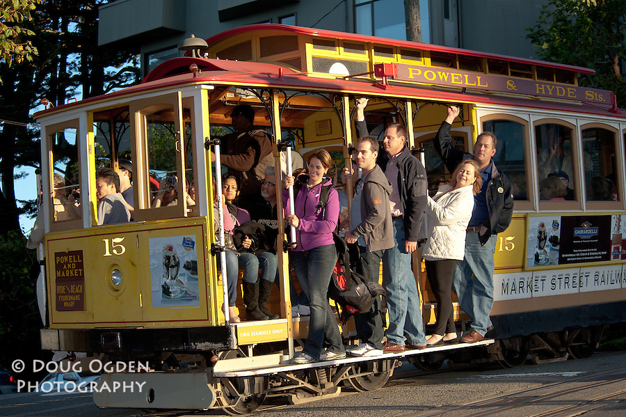 Tourists riding the Powell and Hyde cable car in San Francisco