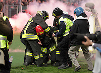 A fireman (C) is assisted by his colleagues after being hit with smoke bombs and firecrackers thrown onto the pitch by Napoli's fans, prior to the Italy Cup final soccer match between ACF Fiorentina and SSC Napoli at the Olimpico stadium in Rome, Italy, 03 May 2014