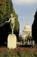 Luxembourg Palace and Gardens. Weathered bronze statue of man in Puckish garb and pose on stone pedestal. Pantheon dome in distance between tree lines. Red-flowered plants around pedestal. Paris, France.