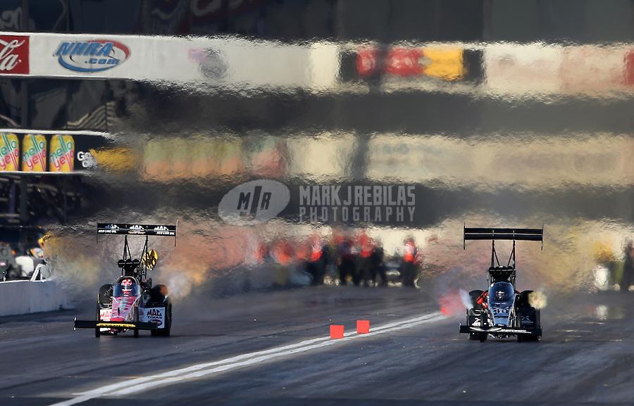 Feb. 16, 2013; Pomona, CA, USA; NHRA top fuel dragster driver Doug Kalitta (left) races alongside Spencer Massey during qualifying for the Winternationals at Auto Club Raceway at Pomona.. Mandatory Credit: Mark J. Rebilas-