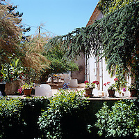 The sunlit stone terrace is surrounded by lush shrubs and trees