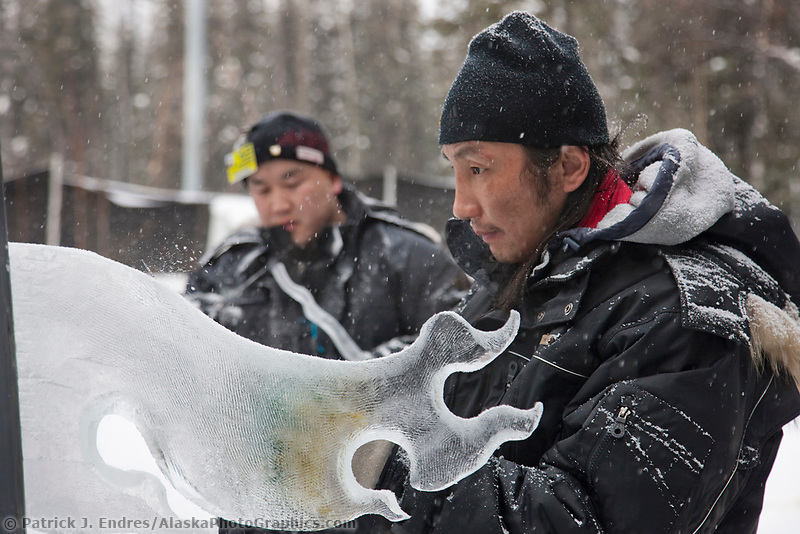 "Mongolian sculptors Rashaanjav Tuvshintur and Tserendash Batmunkh work on the abstract single block sculpture titled ""Evolution"" for the 2009 World Ice Art Championships in Fairbanks, Alaska."