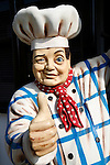 Giant model male chef with traditional chefs hat and clothing winking and showing thumbs up
