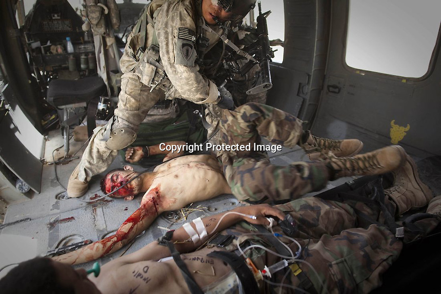"""U.S. Army flight medic Sgt. Jose Rivera from Task Force Lift """"Dust Off"""", Charlie Company 1-214 Aviation Regiment, tends to two badly wounded Afghan national police officers aboard a medevac helicopter after they came under fire in the outskirts of Sangin, in the Helmand Province of southern Afghanistan, Friday, June 3, 2011. """"Wounded"""" Photo by Anja Niedringhaus/The Associated Press"""