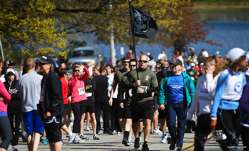 Runner, and member of SERT, Seacoast Emergency Response Team, Seth Tondreault, carries a Portsmouth Police flag as he heads up to the start line for the Chief Maloney Memorial Charity Run/Walk in Portsmouth, N.H., Sunday, April 29, 2012.  (Portsmouth Herald Photo Cheryl Senter)