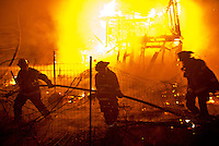 Firefighters pull hose into a fenced area to attack fire that spread to an adjacent building during a three-alarm structure fire on Ward Road in Santa Rosa, Calif., on December 12, 2013. (Alvin Jornada / The Press Democrat)