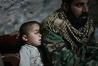 Photographer: Rick Findler..27.04.12 A young boy falls asleep on his fathers arm in a hidden cave in Northern Syria. The cave is used as an operations centre for the Free Syrian Army and house approxiamtely 20 members.