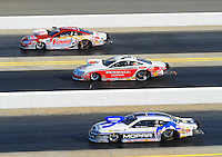 Apr. 13, 2012; Concord, NC, USA: NHRA pro stock drivers (from top) Jason Line, Mike Edwards and Allen Johnson race downtrack during qualifying for the Four Wide Nationals at zMax Dragway. Mandatory Credit: Mark J. Rebilas-