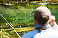 An angler eyes a brown trout on Big Sheep Creek near Dillon, Montana.