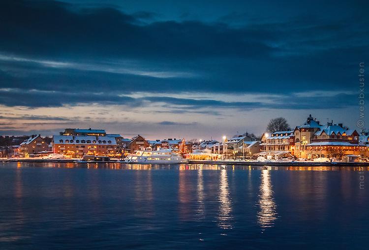 Vinter snö is Waxholmsbåtar och öppet vatten i Vaxholms hamn i Stockholms skärgård.