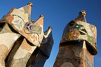 Detail of chimneys, Casa Batllo, 1875-77, renovated 1904-1906, Barcelona, Catalonia, Spain, pictured on January 9, 2007, in the afternoon. Casa Batllo, 43 Passeig de Gracia, was remodelled by Antoni Gaudi and Josep Maria Jujol for Josep Batllo, the owner of the house.  Inspired by the colours and shapes of marine life Gaudi produced an extraordinary building. Its local name is Casa dels ossos (House of Bones). It is decorated with a mosaic made from broken ceramic tiles (trencadis) in shades ranging from orange to greenish blues. The roof may be an allegory of the story of St George (patron saint of Catalonia) and the Dragon, its arch representing the dragon's back. Picture by Manuel Cohen.