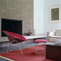 A Harry Bertoia red chair and footstool infront of the modern fireplace in the living area