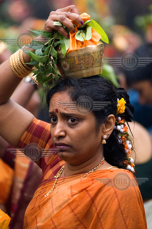 A woman carries offerings on her head for worship at the Sri Lankan Sri Kanaga Thurkkai Amman Temple in Ealing, London.