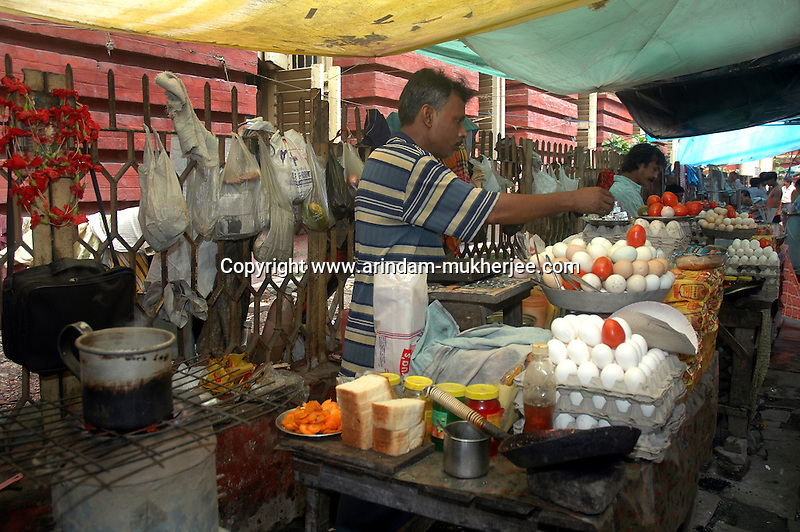 An Indian man at work in his street food stall  at  Dalhousie area of Kolkata. Street food stalls are serving the office goers for decades. All kind of Indian foods are available on the street at an affordable price. They sale them openly. Street food stalls are another results of unempoloyment and over poppulation. They serve millions of people in India. Kolkata, West Bengal,  India  7/18/2007.  Arindam Mukherjee/Landov