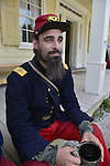 """Old Bethpage, New York, USA. August 30, 2015. ANDREWS PREBLE from Long Beach portrays an American Civil War soldier Captain from the 14th Brooklyn Regiment (14th New York State Militia) AKA The Brooklyn Chasseurs, at the Noon Inn tavern during the Old Time Music Weekend at the Old Bethpage Village Restoration. During their historical reenactments, members of the non-profit 14th Brooklyn Company E wear accurate reproductions of """"The """"Red Legged Devils"""" original Union army uniform."""
