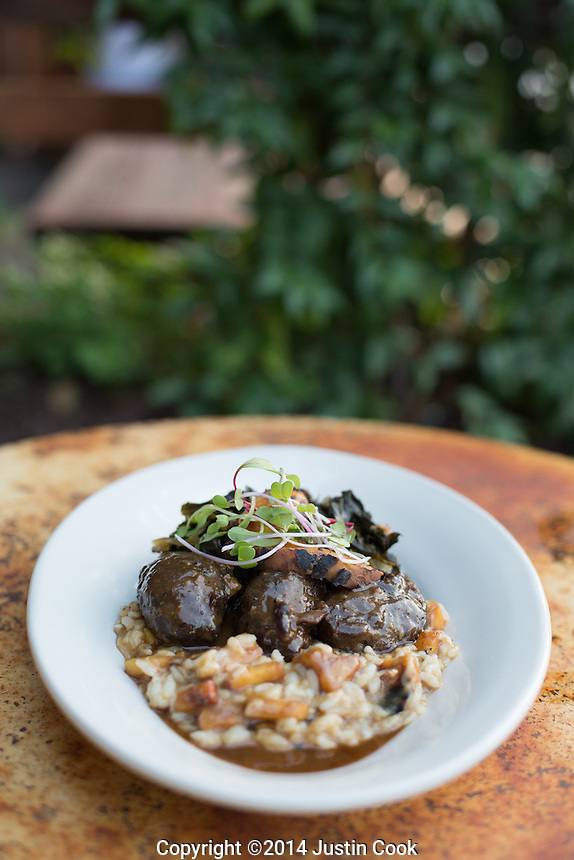 Pork medallions with peach risotto and collard greens at Farm Table in Wake Forest, N.C. on Wednesday, September 17, 2014. (Justin Cook)