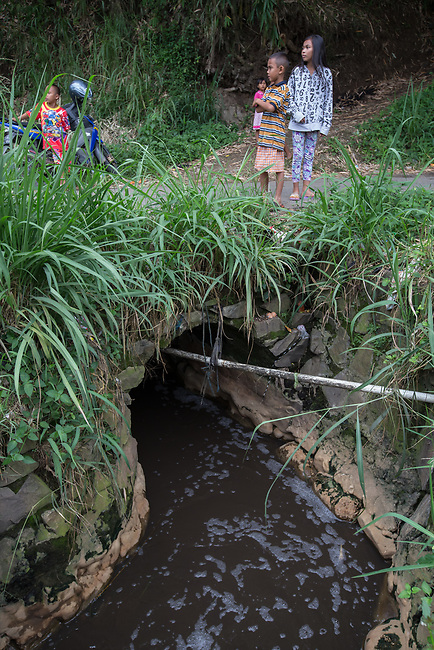 29 JAN, 2018, Bandung, Indonesia: Kids play around a toxic canal used by five industrial companies to dump untreated waste including dyes that feeds into the Citarum river, listed as one of the most polluted rivers in the world.  It will soon be the main water supply system for Jakarta as the bores that have been dug into the aquifers dry but it also supports agriculture, fishery, industry, sewerage and electricity.  The Indonesian Government is moving to urgently try to clean the system up but it is fighting massive infrastructure issues and toxic industrial dumping.    Picture by Graham Crouch/The Australian