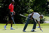 United States President Barack Obama, right, picks up a club while playing a round of golf with Ray Allen, left, on the first green at the Farm Neck Golf Club in Oak Bluffs, Massachusetts, U.S., on Saturday, August 9, 2014.  The President is vacationing on the island for two weeks.  <br /> Credit: Matthew Healey / Pool via CNP
