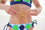 USA, Florida, St. Pete Beach, Girl (8-9) holding starfish in front of stomach on beach, mid section
