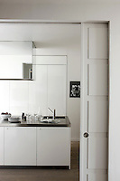 The bespoke kitchen is constructed entirely from lacquered white polyester and stainless steel polished to a mirror finish
