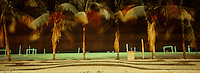 Palm trees at Calcadao in Copacabana beach ( Copacabana beach sidewalk ) at night, beach soccer field in background, Rio de Janeiro, Brazil.