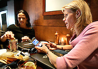 Sports agent Molly Fletcher (right) has lunch with friend Heidi DeRosa--whose husband, Mark DeRosa, is one of Fletcher's baseball clients--at Garrison's Broiler and Tap in Vinings on Wednesday morning, March 22, 2006. Fletcher juggles a busy family life with her more than full-time job representing several top sports personalities.<br />