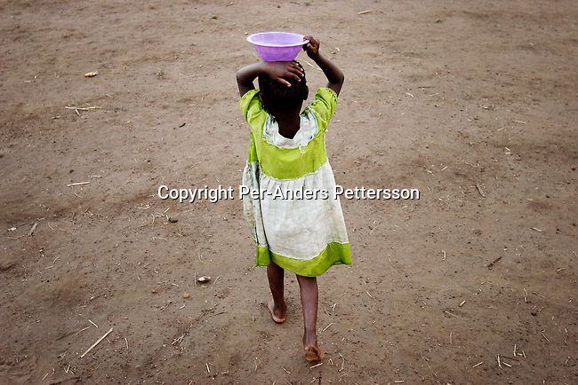 GALUFU, MALAWI OCTOBER 13: An unidentified girl carries a bowl of water on her head, from a water hole on October 13, 2005 in Galufu, Malawi. The ground is dry. It has not rained in the village for months. Most people in the village are poor and hungry, and cannot afford to buy maize at the market as the price is twice as much as the government subsidized prices. The government used to sell subsidized maize and fertilizer but not anymore.  Many in the village eat mangoes and even boil unripe ones, as they cannot afford to buy anything else. The harvest was very bad in 2005 and the next one, due in April 2006 I uncertain because of lack of rains and drought. The village has seen an increase in poverty the last few years due to drought and HIV/Aids. Southern Africa has been hit by a severe hunger crisis due to drought and poverty. An ever-increasing HIV/Aids rate adds to the misery. Malawi is one of the worst hit areas and Galufu village is a typical small village that has become victim of this poverty spiral. (Photo by Per-Anders Pettersson)