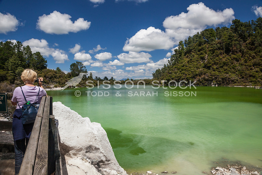 Tourist looking at Lake Ngakoro (the Green Lake) at Waiotapu, Rotorua, New Zealand - stock photo, canvas, fine art print