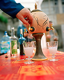 SWITZERLAND, Couvet, an Absinthe fountain fills glasses outside of the Artemisia Distillerie, Jura Region