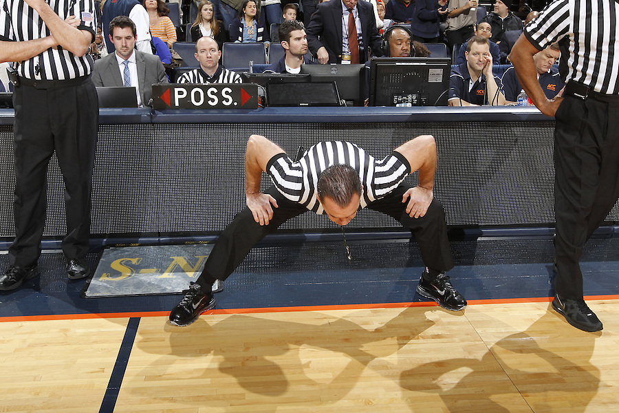NCAA referees stretch on the court before the game Saturday in Charlottesville, VA. Virginia won 65-45.