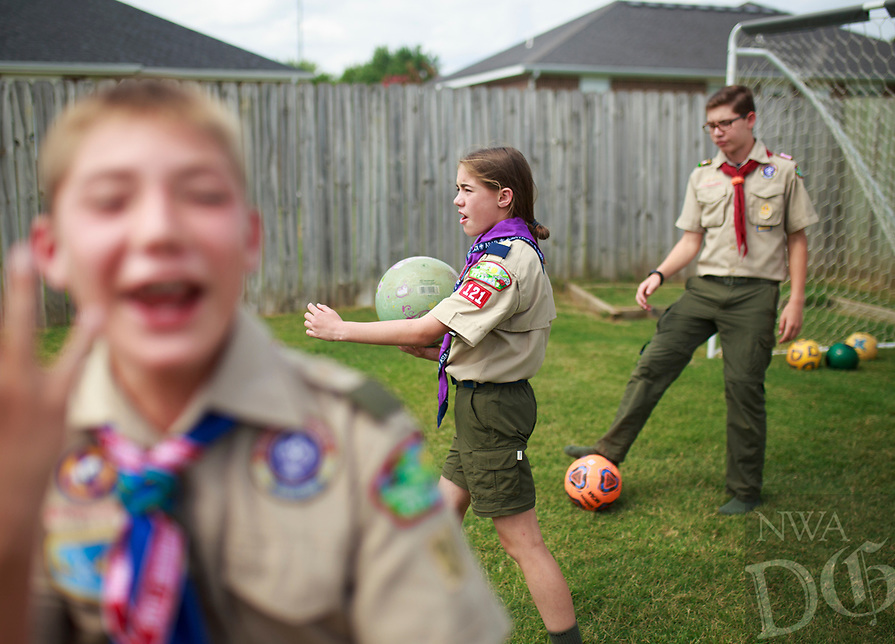 NWA Democrat-Gazette/CHARLIE KAIJO Ruby Freeman (center) and brothers Michael (left) and Matthew (right) play soccer, Saturday, July 14, 2018 at their home in Bentonville.