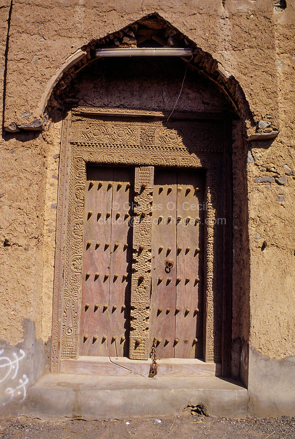 """Mudhaireb (Mudayrib), Oman.  Old Door, Carved in Zanzibar, dated 1208 A.H., equals 1793 A.D.  """"God is the Best Protection"""" carved in Arabic above the door."""