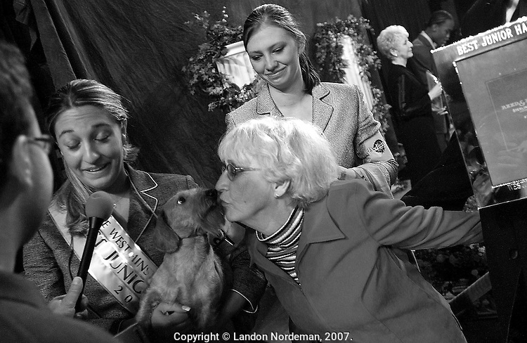 "NEW YORK - FEB 10:  Katie Shepard, 18, left, from Kansas City, speaks to an interviewer from the ""Pet News"" radio show as her grandmother bestows a congratulatory kiss on her wirehaired daschund, ""Champion H'Rtlndhls Tickle Me Elmo"" after Katie won the ""Best junior Showmanship"" award at the 128th Annual Westminster Kennel Club Dog Show at Madison Square Garden in New York City on Tuesday February 10, 2004. (Photo By Landon Nordeman)"