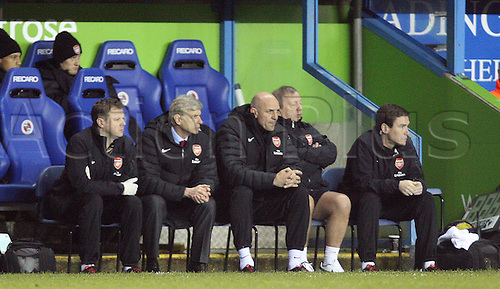 17.12.2012. Reading, England. ..Arsene Wenger Manager of Arsenal and Asst Manager Steve Bould..watch from the dugoout during the Premier League match between Reading and Arsenal from Madejski Stadium