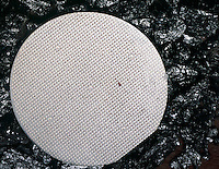 SILICON WAFER<br /> Nestled On A Bed Of Elemental Silicon<br /> Manufactured silicon wafer which has been silk-screened for etching, used to make integrated circuit (IC) chips. This sample has a manufacturer defect.