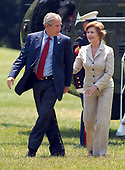 Washington, D.C. - July 8, 2007 -- United States President George W. Bush and first lady Laura Bush walk across the South Lawn as they return to the White House aboard Marine 1 from a week-end at Camp David.<br /> Credit: Ron Sachs  - Pool via CNP