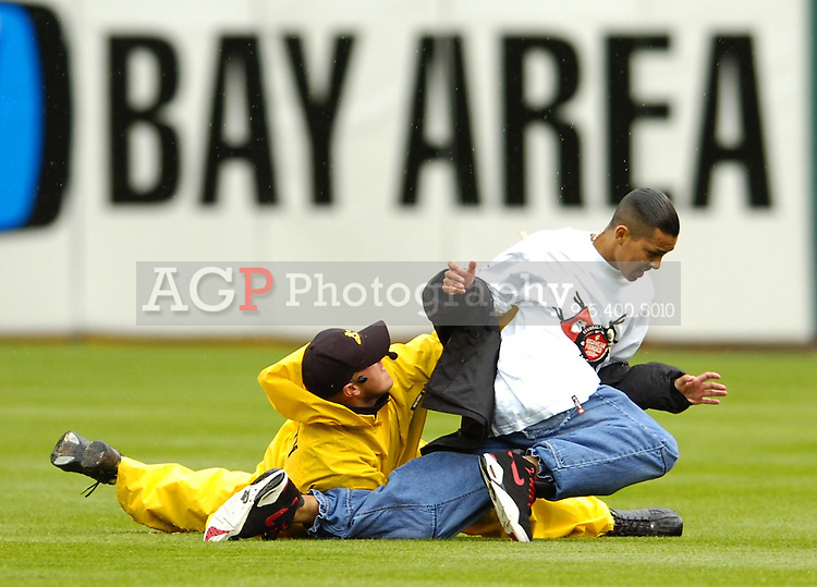 A fan is tackled by a security officer after running onto the field between the 8th and 9th innings of the Chicago White Sox-Oakland Athletics game at the McAfee Coliseum Wednesday April 27, 2005, in Oakland, Calif. The fan was escorted from the field by police and coliseum security officers. (photo by Alan Greth)
