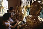 Children rub gold leaf onto images of Buddha in Bangkok, Thailand. (Jim Bryant Photo).....