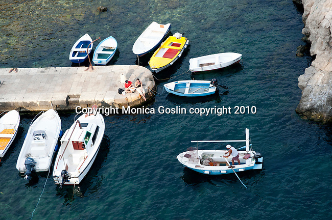 Two people sit on a stone pier and watch a man rowing a boat into shore in Dubrovnik, Croatia.